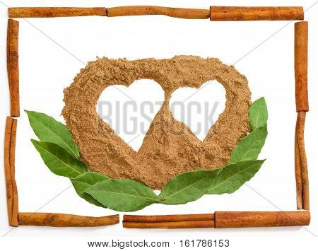 Pile of powder cinnamon in the shape of a two hearts and a bay leaves with a frame made up of cinnamon sticks on a light background