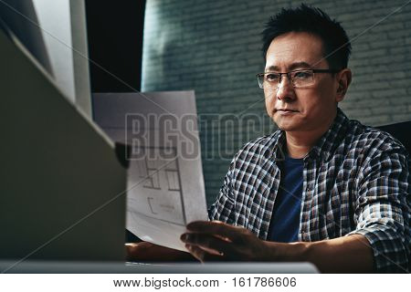 Concentrated Singaporean architect looking at blueprint of apartment
