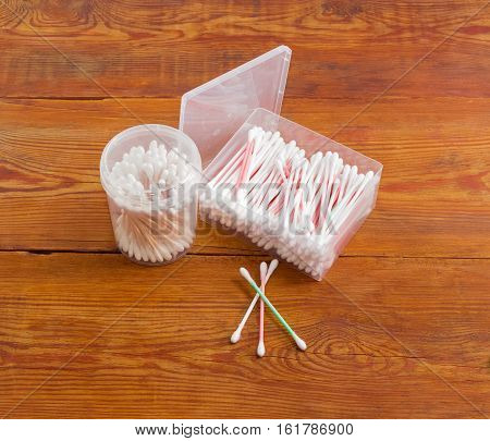 Cotton swabs on a plastic rods in rectangular plastic container cotton swabs on a wooden rods in round plastic container and several cotton buds separately on old wooden planks