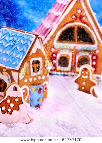 Gingerbread man , house near tree Christmas cookie with blue sky and falling winter snow. Xmas food decoration is designed as sweets country lodge. It can be used as holiday cards.
