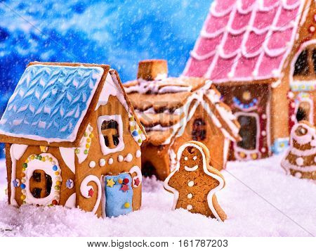 Gingerbread man , house near tree Christmas cookie with blue sky and falling winter snow. Xmas food decoration is designed as sweets country lodge.