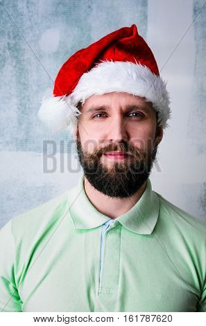 Christmas celebration portrait of young adult bearded happy man wearing Santa hat