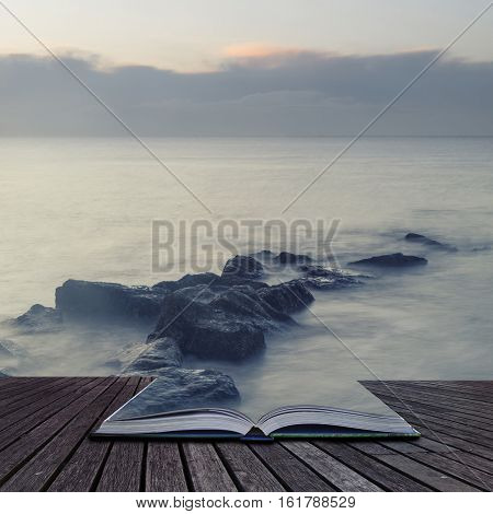 Peaceful Cross Processed Landscape Image Of Calm Sea Over Rocks At Dawn Coming Out Of Pages Of Book