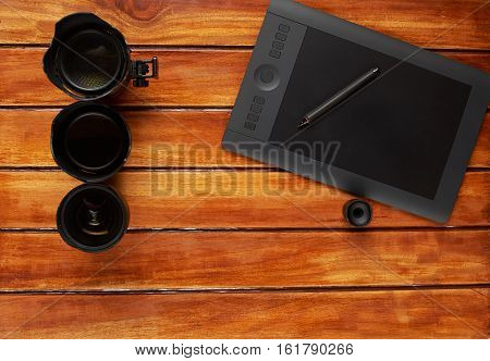 Photography dlsr lens on wood table with graphic designer tablet