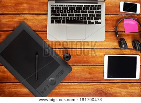 Gadgets of retoucher on brown wooden table. Modern laptop, tablet, smartphone, headphones view from top