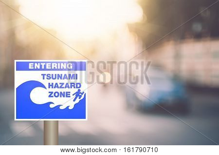 Tsunami Hazard Zone Warning Sign On Blur Traffic Road With Colorful Bokeh Light Abstract Background.