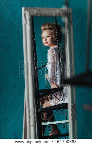 reflection in the mirror Beautiful blond bride in white negligee sitting on the black wrought iron stairs