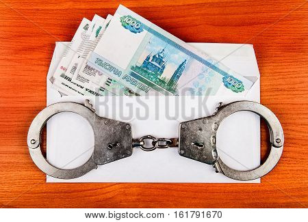 Handcuffs on the Envelope with Russian Rubles on the Table