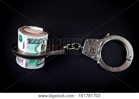 Russian Rubles and Handcuffs on the Black Background