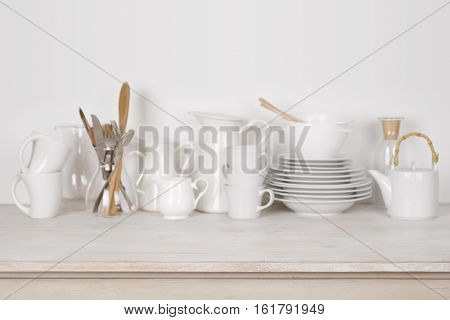 Blurred kitchen dishware background on wooden table with copy space