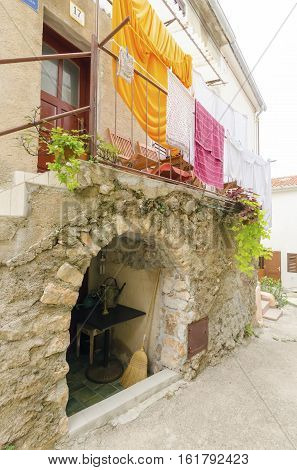 Traditional picturesque Mediterranean architecture at medieval town Vrbnik on Krk island Croatia. View of stone houses arched narrow alley balcony and flowers.