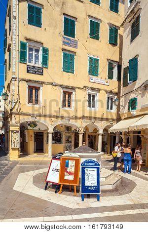 Corfu, Greece - July 1, 2011: Tourists Stand Near Advertising Pillars Philharmonic