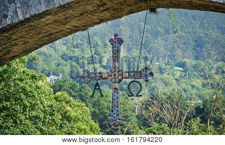 Closeup view of hanging cross under roman bridge of Cangas de Onis, Principado de Asturias, Spain