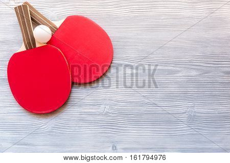 Red racket for ping pong ball on gray wooden background top view