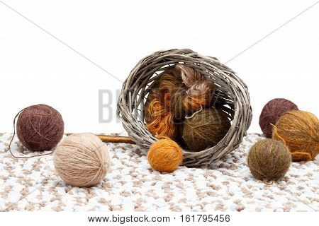 Colorful yarn in tangle and coil in overturned braided basket near tangles of yarn and wooden spokes. isolated on white background