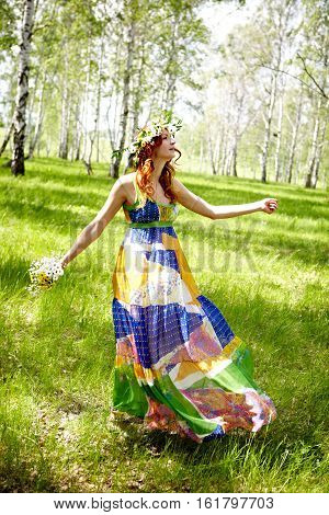 Young woman in sundress walking in meadow
