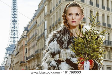Trendy Woman With Christmas Tree In Paris, France Looking Aside