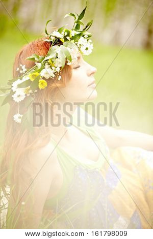 Young woman in flower crown relaxing under summer sun
