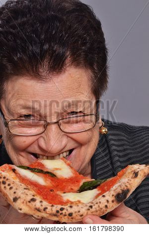 Happy grandmother eat pizza.