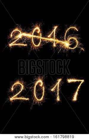 Strikethrough 2016 and 2017 digits made of sparkling light isolated on black background. Old year going new year comming.