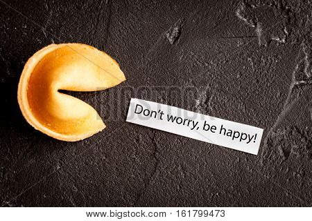 Chinese fortune cookie with prediction on dark background close up top view