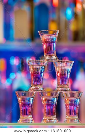Pyramid of six shot glasses with cocktails standing on a bar counter