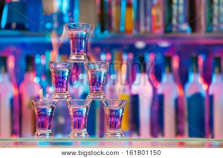 Picture of pyramid line of burning alcohol cocktails standing on a bar counter with copy-space