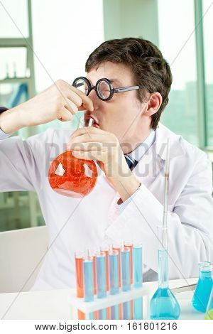 Scientist drinking tasting chemical in chemical lab