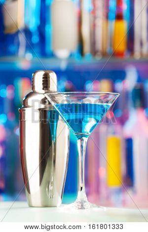 Close-up picture of martini glass filled with blue liquor and shaker standing on a bar counter