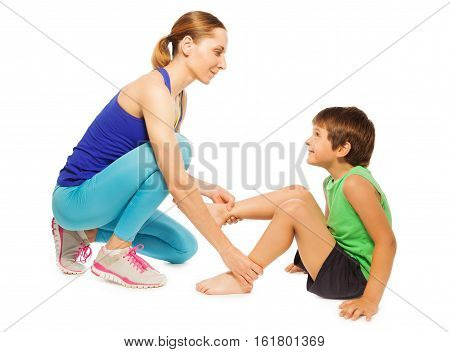 Side view portrait of female trainer helping kid boy making gymnastics, isolated on white