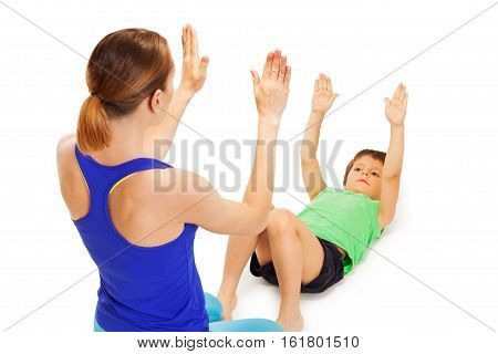 Kid boy repeating physical exercises, laying flat on back after trainer, isolated on white