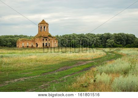 Thrown old church on a green countryside meadow