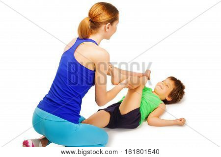 Female trainer helping little boy crossing knees to elbows, laying flat on back, isolated on white