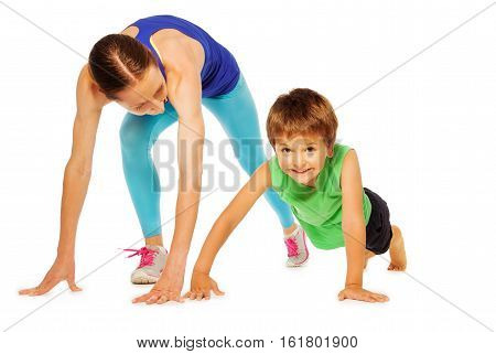 Sporty mother doing pushing ups with her kid son, isolated on white