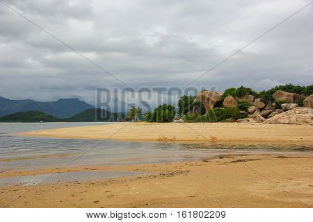 a pile of large boulders on the beach surrounded by green plants, yellow sand, clear sea water, mountains on the horizon, the sky overcast, gloomy