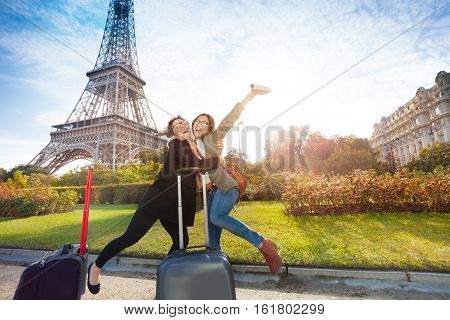 Two happy friends, female tourists, meeting in Paris near the Eiffel Tower