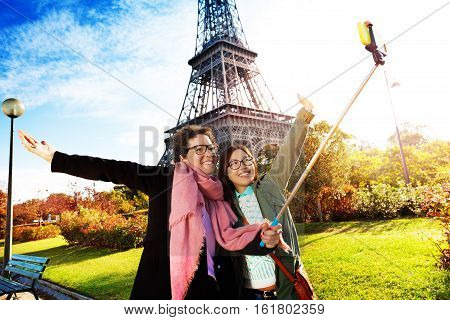 Two smiling female tourists taking selfie photo with stick against the Eiffel Tower, Paris