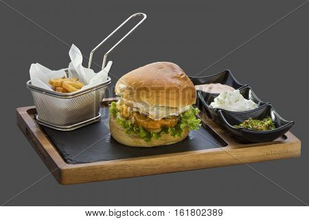 Burger with fried meat garnish fried potatoes and three kinds of sauce served in a bowl made of wood and stone