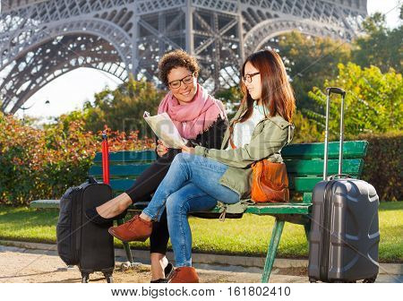 Two beautiful women sitting on a bench and reading map of Paris with Eiffel tour on background