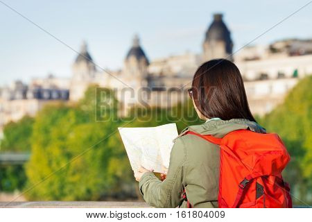 Young girl with big red backpack looking to the traveler guide book of Paris