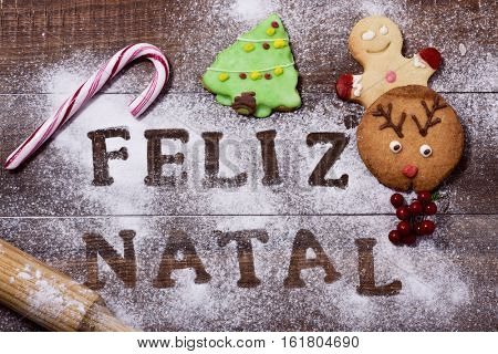 high-angle shot of a wooden table sprinkled with icing sugar or flour where you can read the text feliz natal, merry christmas in portuguese, a rolling pin, some candy canes and some christmas cookies