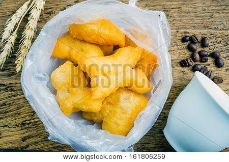 Chinese deep fried dough sticks in plastic bag place on old wooden breakfast in Thailand