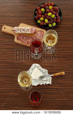 Glasses with wine, grape, wurst and cheese on wooden background