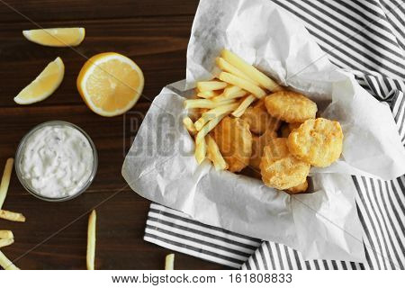 Tasty chicken nuggets with fries, sauce and lemon on table