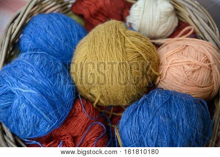 Multicilored wool clews in wood basket. Illustration about wool needlework and knitting