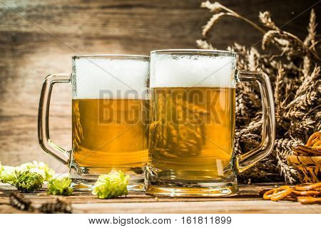 Two tankard beer closeup on wooden table and empty wooden background