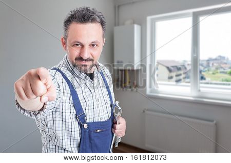 Handsome fitter with steel wrench pointing finger at you in the house with copy space poster