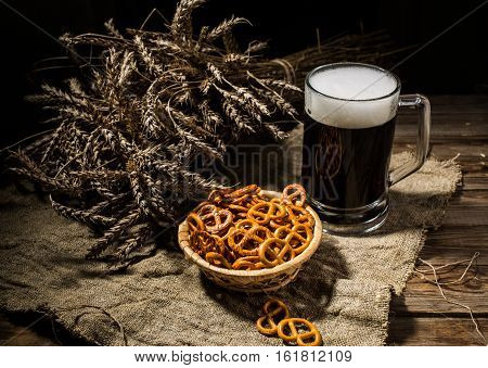 Mug beer with wheat and basket of pretzels on linen cloth on wooden table