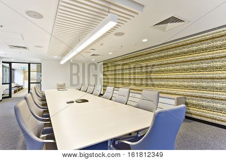 Close view of a modern meeting room with tables and chairs in front of the wall pattern design under turned on the lights