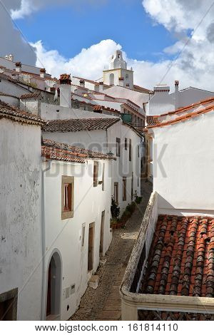 MARVAO, PORTUGAL: A typical cobbled street with whitewashed houses and tiled roofs with the Clock Tower in the background